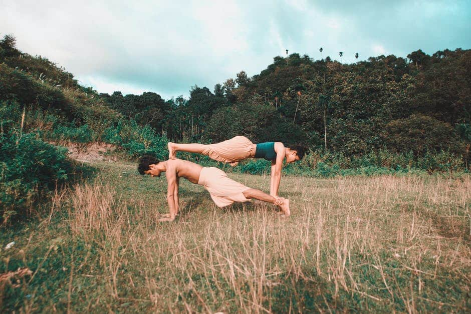 two person doing yoga in a field